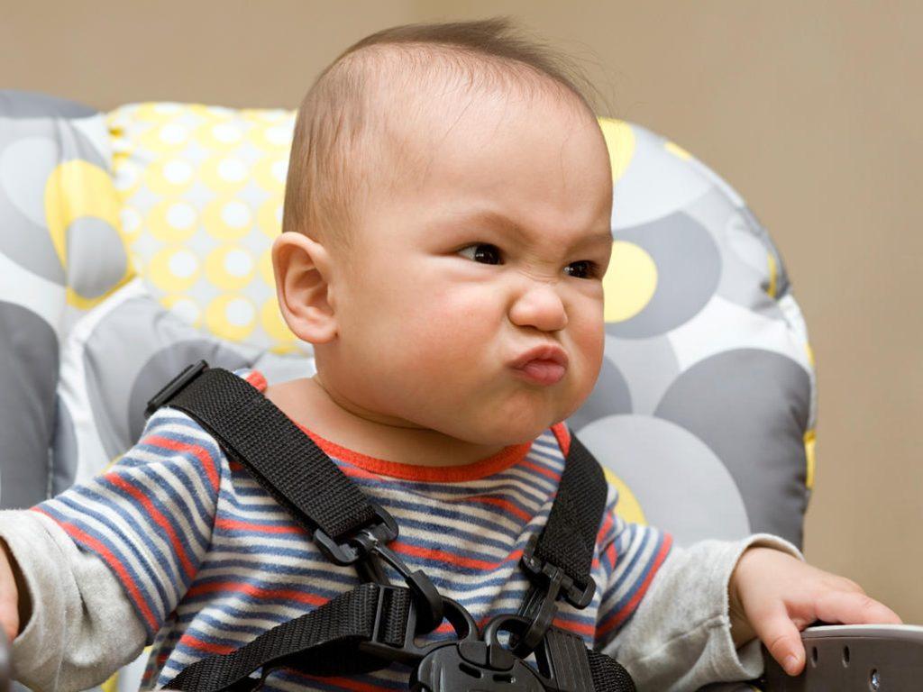 Bebê com descendência oriental com camiseta listrada, preso em um cadeirão, fazendo careta.